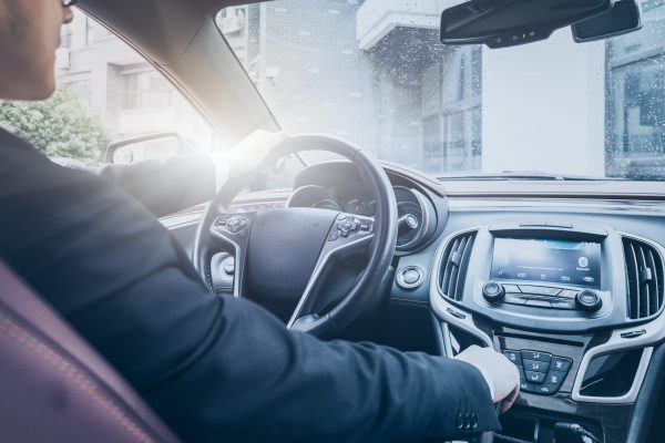 detail shot of young businessman driving his car.