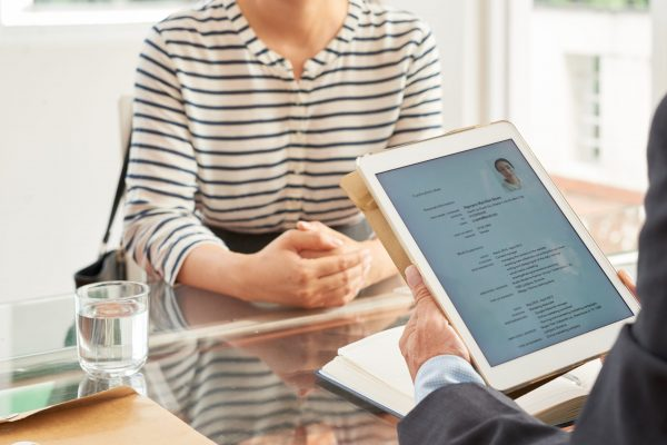 Businessman reading resume of woman on his digital tablet during an interview